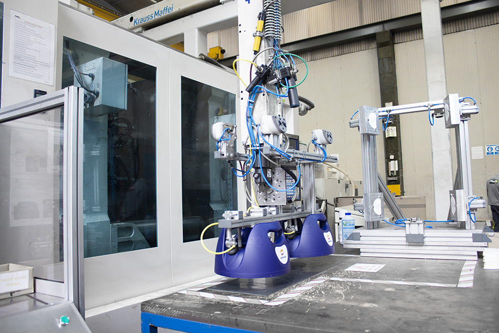 Repsol handles taken out of mold by krauss maffei injection machine robot
