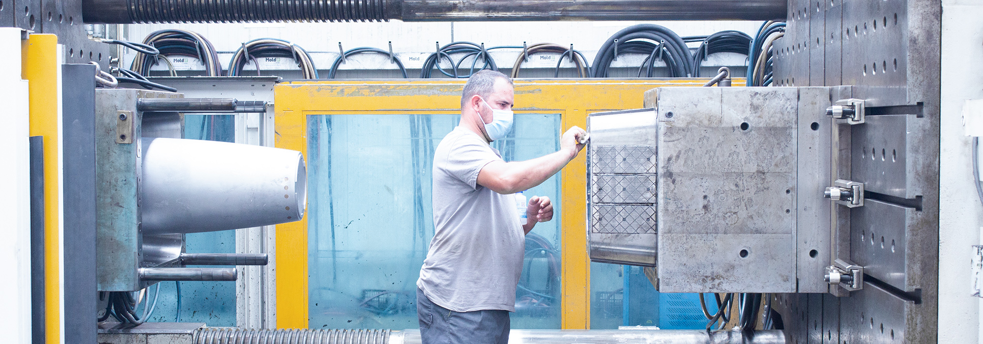man cleaning artvasi vase mold in injection machine at MOLDIT Industries