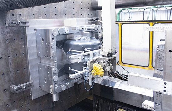 plastic automotive wheel arch being taken out of mold by injection machine robot
