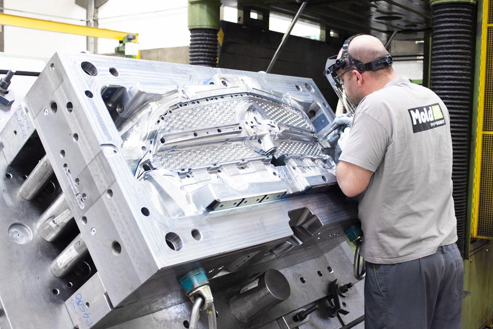 worker polishing front bumper steel mold