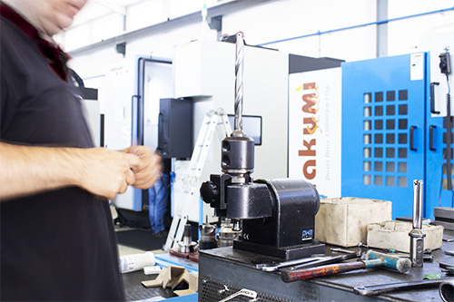 worker with drill in clamp in workbench at CF Moldes